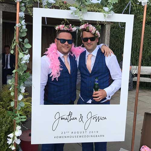 Two Groomsmen wearing sunglasses standing behind copper arch polaroid prop photobooth at a wedding holding a beer