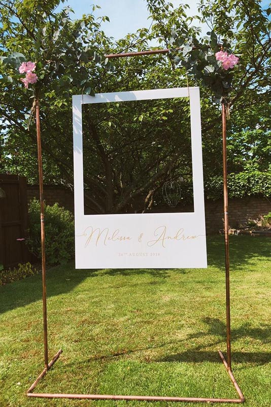 Beautiful Copper Arch with a hanging Polaroid Prop Wedding Garden