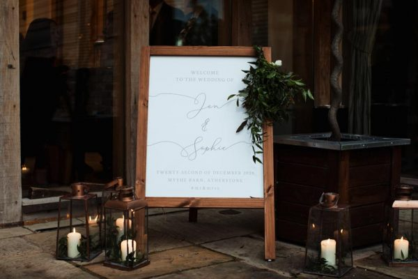 Wooden Welcome Sign at Wedding Entrance surrounded by Candles